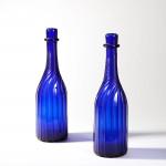 A pair of blue glass bottles