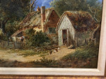Extensive English landscape with a man on a pathway travelling through a village past a cottage