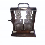 Miniature Victorian oak and silver plate tantalus with two cut glass bottles