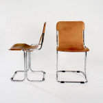 A set of four chromed tubular metal chairs with slung leather seats
