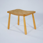 A maple stool with turned legs and a webbed saddle seat