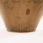 A large earthernware vase with an ochre glaze and incised decoration