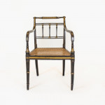 A Regency ebonised and gilt elbow chair