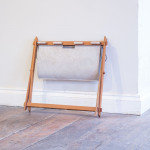A teak and suede x frame magazine holder