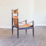 A high back 'Safari Chair' with slung tan leather seat, back and arms by Erik Worts