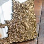 An unusual repousse gilt brass easel mirror