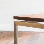 A rectangular polished steel and teak coffee table
