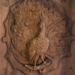 A limewood carving of a peacock in a carved walnut glazed case