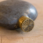 A fine small circular pewter pocket flask with chased decoration
