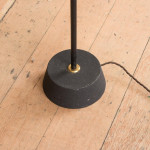 A simple black and patinated brass floor lamp