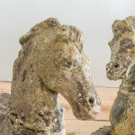 A pair of weathered composite stone recumbent horses