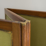 A large four fold cherrywood and upholstered screen