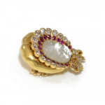 A Carved Moonstone, Ruby & Diamond Baby's Face Brooch