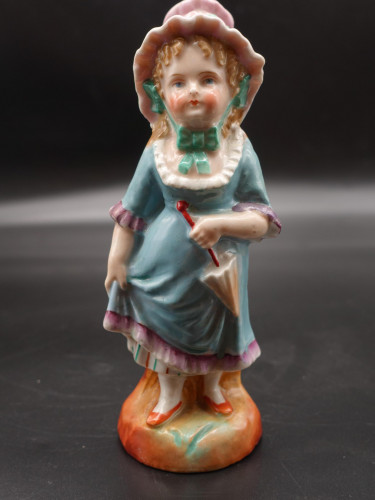 A mid 20th Century Continental Figure of Young Child in a Frilly Hat.