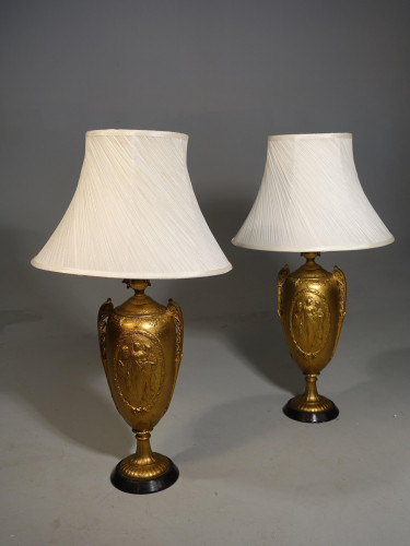 An Early 20th Pair of Neoclassical Shaped Gilded Metal Lamps